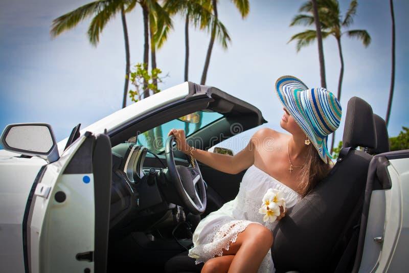 Härlig ung kvinna som vilar i hennes bil arkivbild