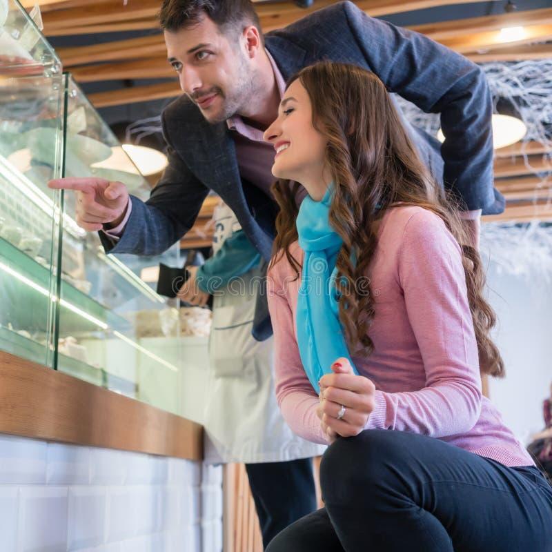 Härlig ung kvinna som visar en i lager kaka till hennes pojkvän royaltyfri fotografi