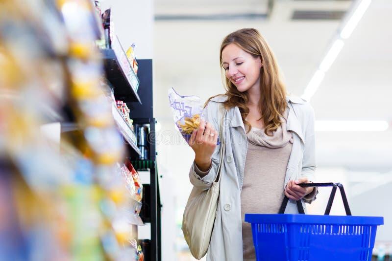 Härlig ung kvinnashopping i en livsmedelsbutik/en supermarket fotografering för bildbyråer