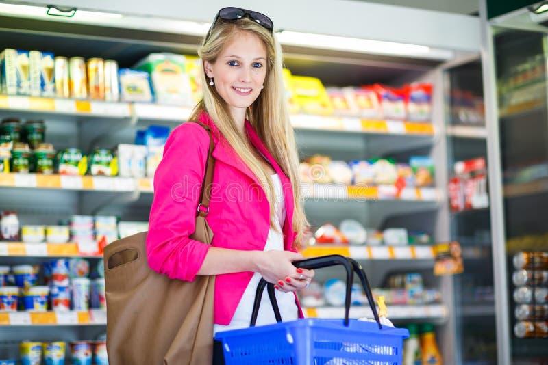 Härlig ung kvinnashopping i en livsmedelsbutik/en supermarket royaltyfria foton