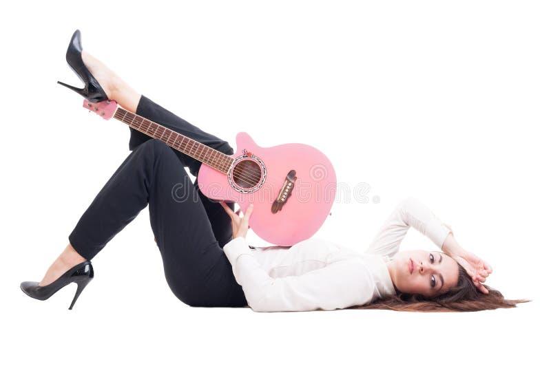 Härlig ung kvinnlig gitarrist som ner ligger på det vita golvet fotografering för bildbyråer