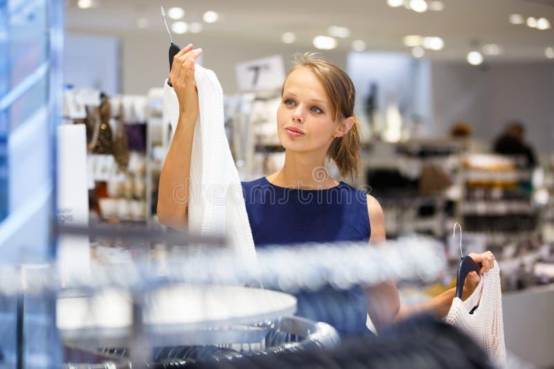 Härlig ung kvinnlig shoppare i ett klädlager royaltyfri bild