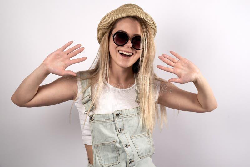 Härlig ung kvinnlig tonåring i solglasögon och hatten som poserar för royaltyfri bild
