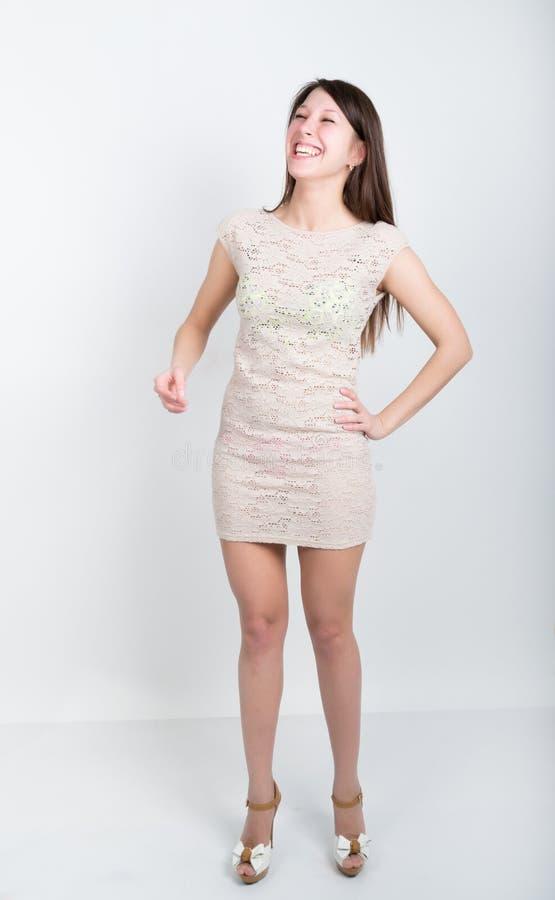 Härlig ung långbent brunett i lite grå full höjd för coctailklänning för flicka skratt mycket, kraftiga sinnesrörelser arkivfoton
