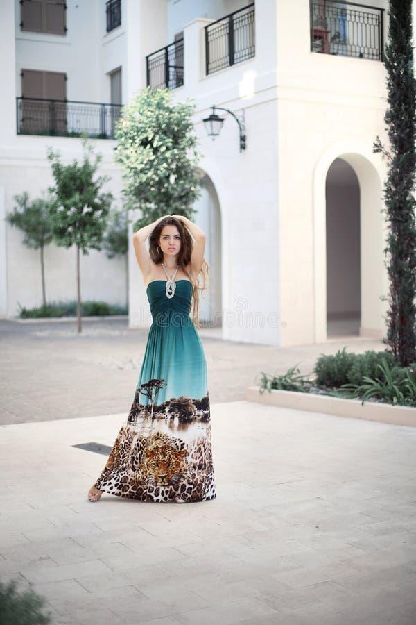Härlig ung le flicka med den långa modeklänningen i marien royaltyfri bild