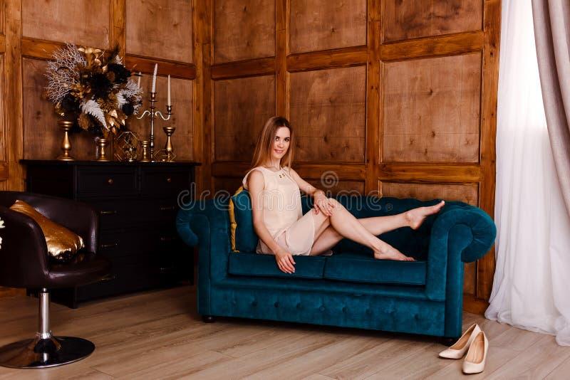 Härlig ung le kvinna i den beigea klänningen som sitter på den gröna sammetsoffan royaltyfria foton