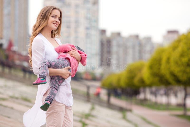 Härlig ung le kvinna med barnet på stads- bakgrund royaltyfria foton