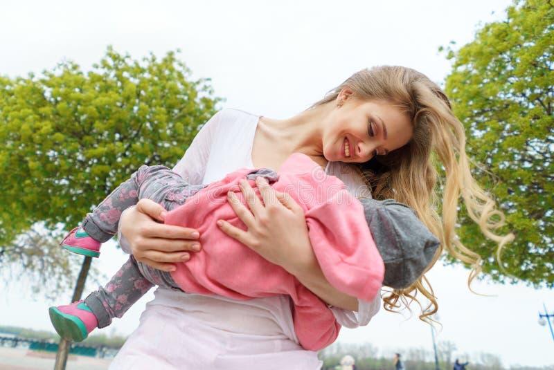 Härlig ung le kvinna med barnet på stads- bakgrund arkivfoton