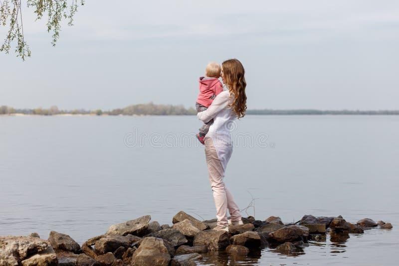 Härlig ung le kvinna med barnet på stads- bakgrund royaltyfri fotografi