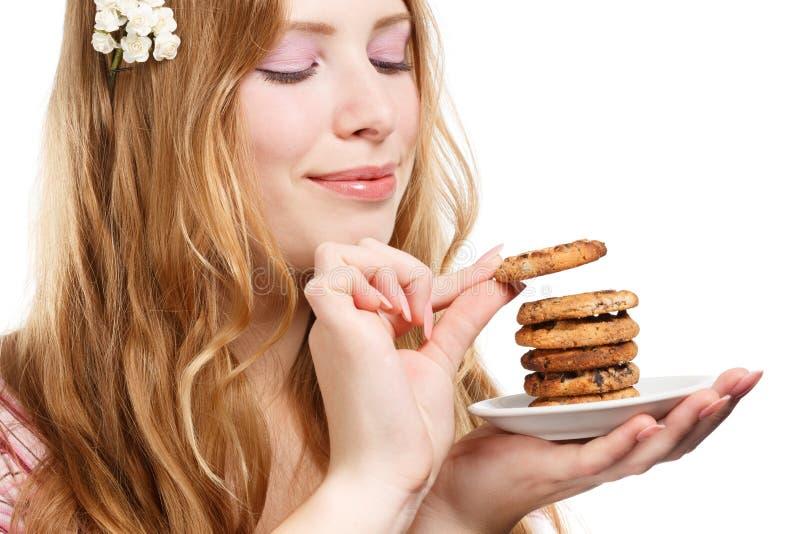 Härlig ung le kvinna med kakor arkivfoton