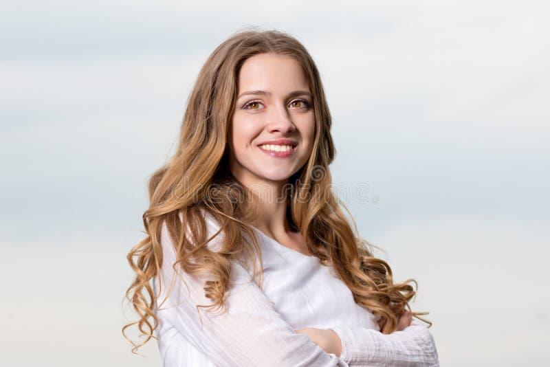 Härlig ung le kvinna på himmelbakgrund arkivbild