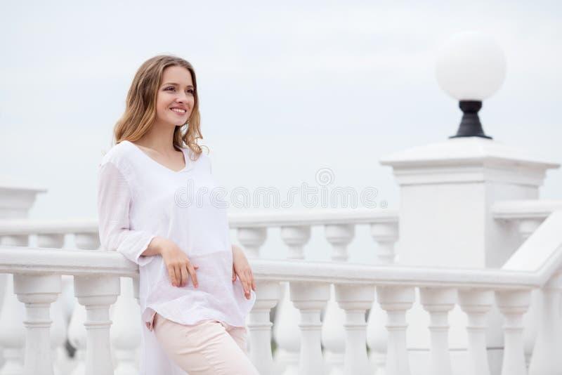 Härlig ung le kvinna på stads- bakgrund royaltyfria bilder