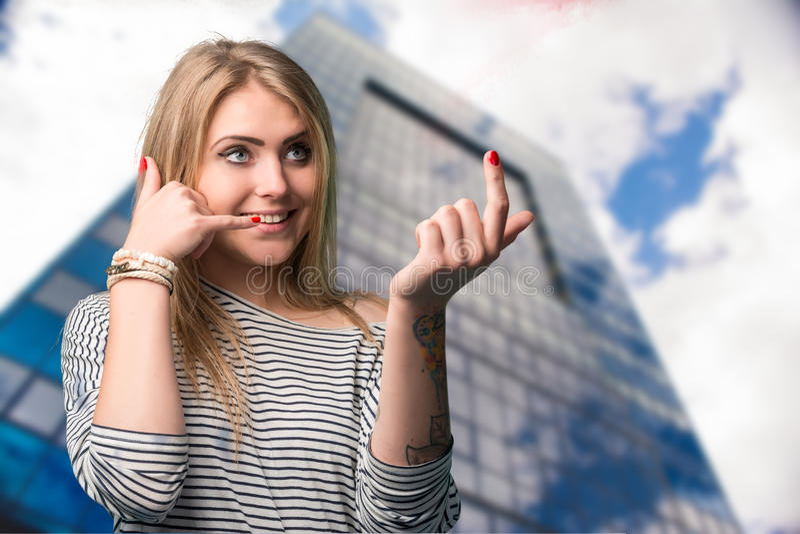 Härlig ung le kvinna som gör en gest det near örat för mobiltelefon royaltyfri fotografi