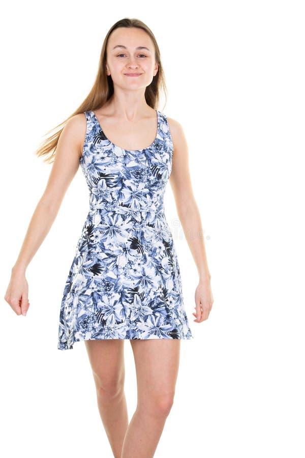 Härlig ung le tonårig flicka i blå blommaklänning på vit bakgrund arkivbild
