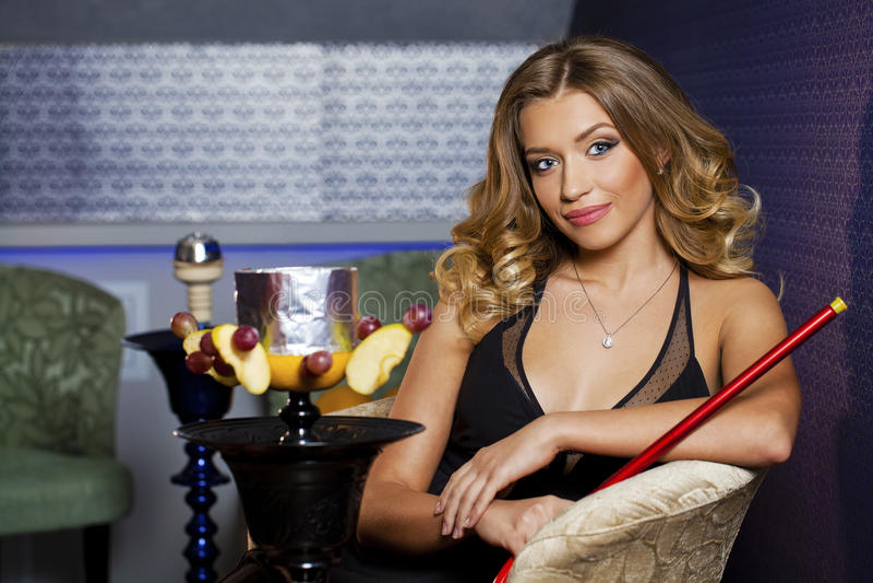 Härlig ung lockig blond kvinna som vilar i vattenpiparummet royaltyfria bilder