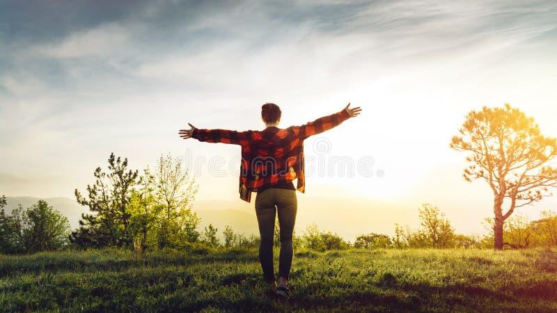 Härlig ung lyckad flicka med öppna armar som tycker om soluppgång och det pittoreska landskapet, bakre sikt arkivbilder