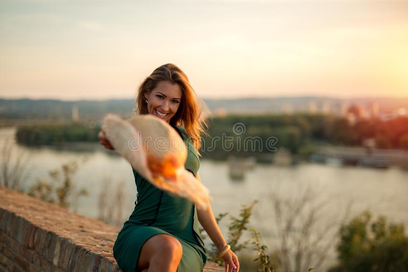 Härlig ung lycklig kvinna som kastar en hatt in i kameran på su arkivbild