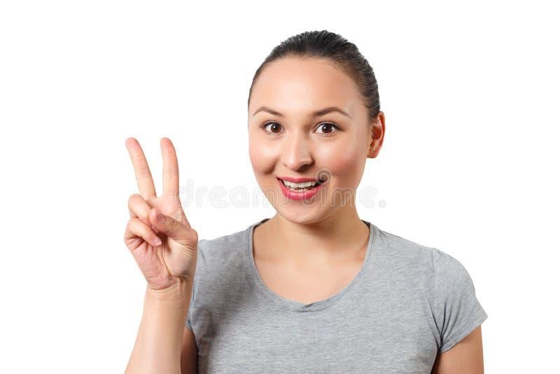 Härlig ung lycklig le victopy flickauppvisning sjunger med hennes hand Fredbegrepp Tecken av gester Isolerat p? vit Det ?r fotografering för bildbyråer