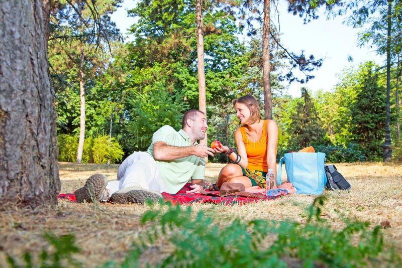 Härlig ung man och kvinna på picknick i skog arkivfoto
