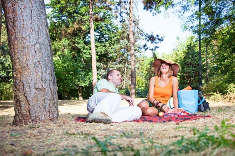 Härlig ung man och kvinna på picknick i skog royaltyfri fotografi