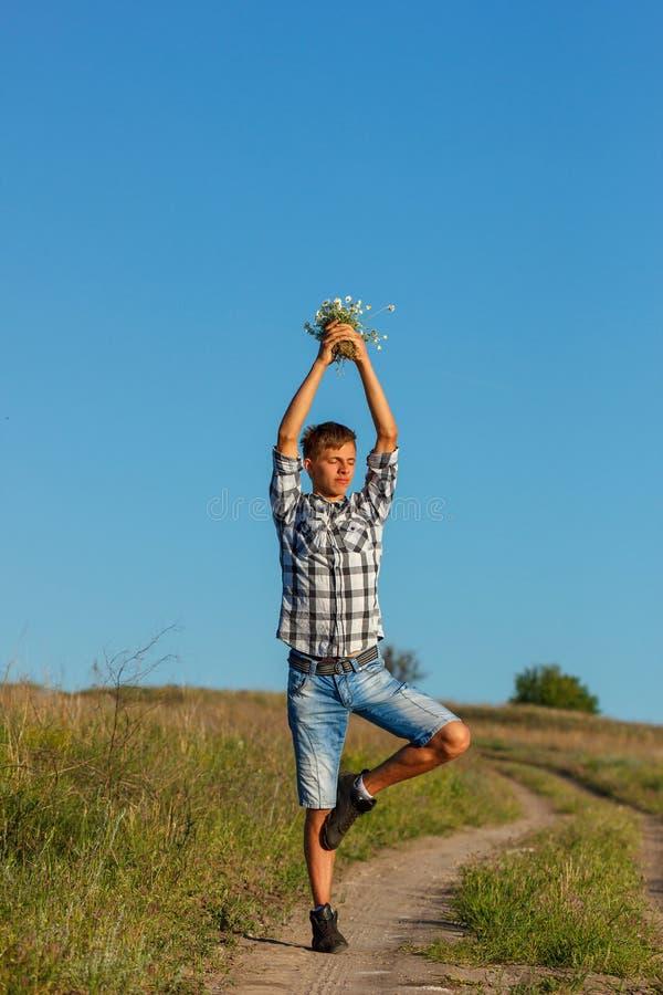 Härlig ung man som gör yoga på vägen på en solig dag royaltyfria foton