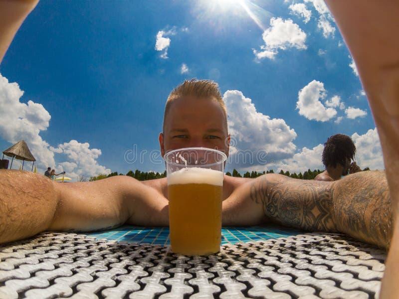 Härlig ung man som tycker om öl på pölen arkivbild