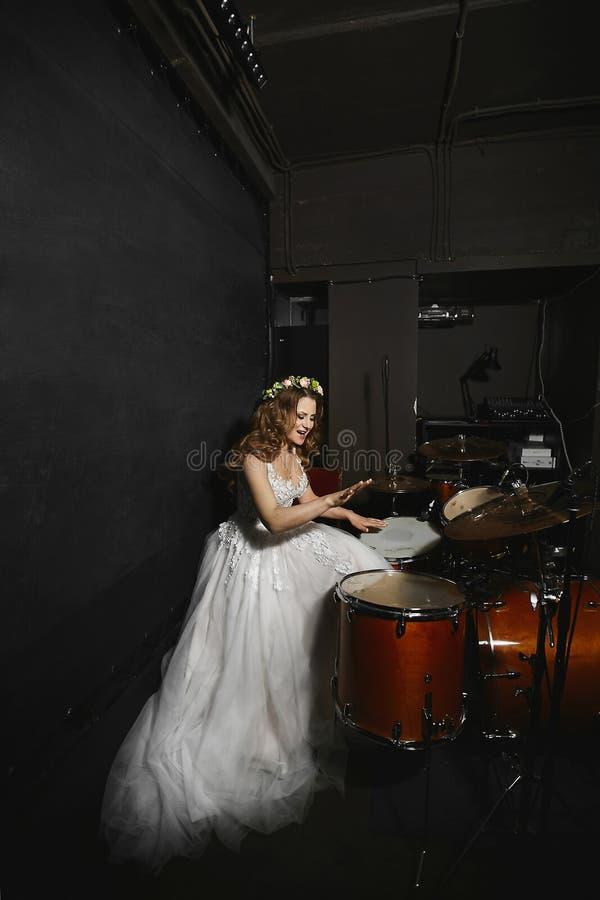 H?rlig ung modellkvinna med att gifta sig frisyren i en br?llopskl?nning som spelar p? valsar fotografering för bildbyråer