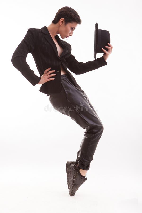 Härlig ung modemodell i eleganta kläder som poserar som Michael jackson som rymmer en stilfull hatt i studio över vit arkivfoto