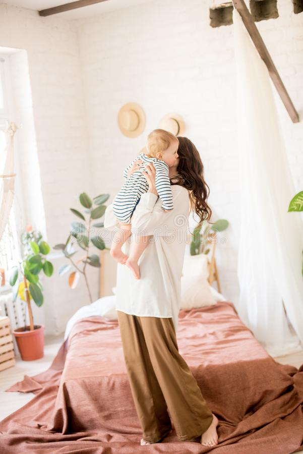 Härlig ung moder med långt mörkt hår i enkla bekväma kläderlekar med hennes unga son i ett hemtrevligt sovrum fotografering för bildbyråer