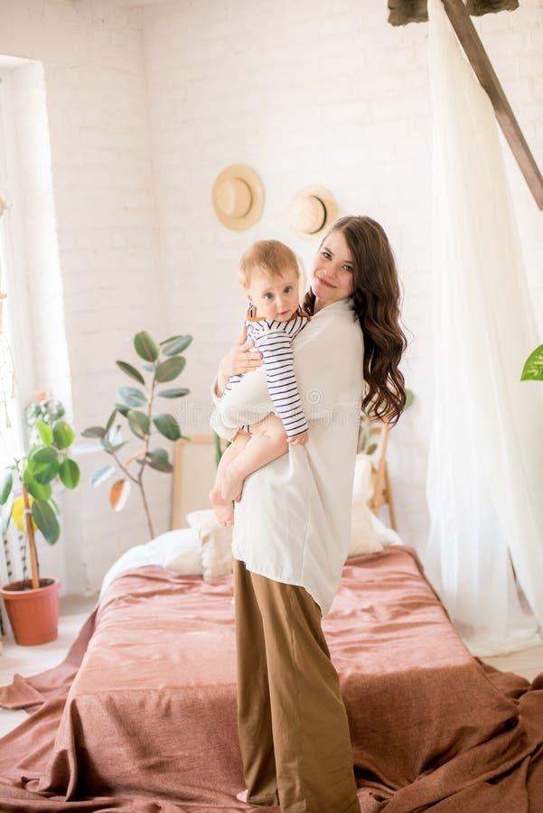 Härlig ung moder med långt mörkt hår i enkla bekväma kläderlekar med hennes unga son i ett hemtrevligt sovrum arkivbild