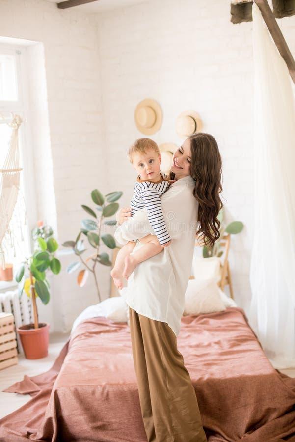 Härlig ung moder med långt mörkt hår i enkla bekväma kläderlekar med hennes unga son i ett hemtrevligt sovrum arkivfoton
