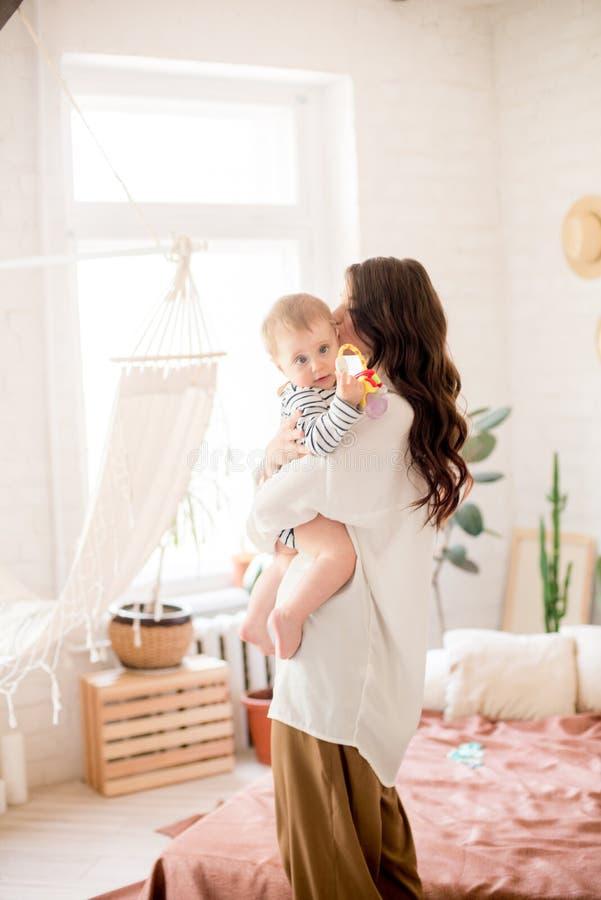 Härlig ung moder med långt mörkt hår i enkla bekväma kläderlekar med hennes unga son i ett hemtrevligt sovrum arkivbilder