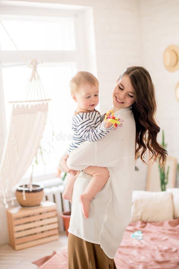 Härlig ung moder med långt mörkt hår i enkla bekväma kläderlekar med hennes unga son i ett hemtrevligt sovrum royaltyfri foto