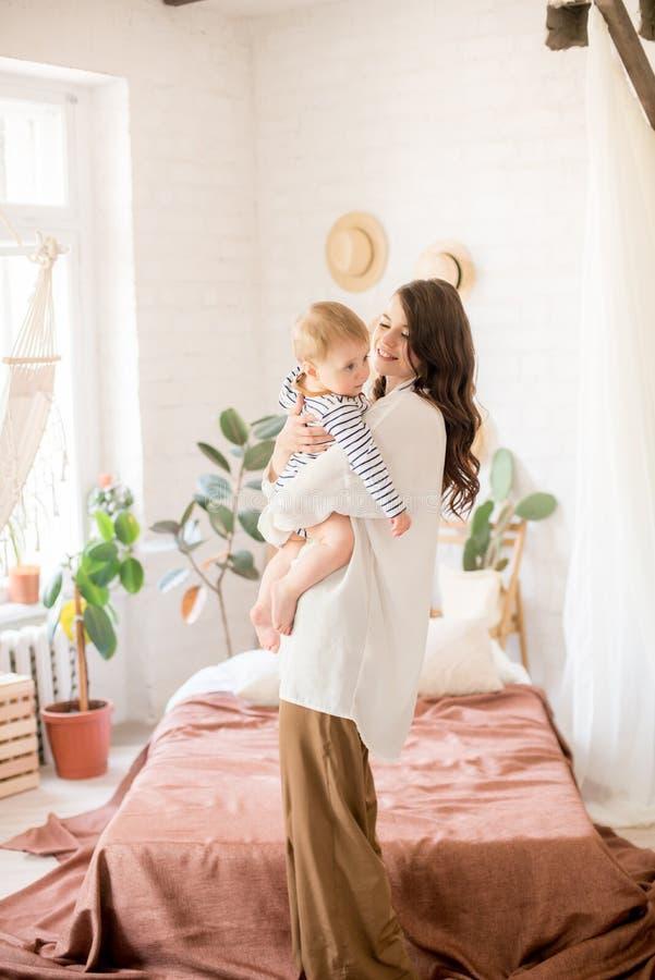 Härlig ung moder med långt mörkt hår i enkla bekväma kläderlekar med hennes unga son i ett hemtrevligt sovrum royaltyfri bild