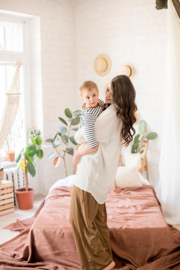 Härlig ung moder med långt mörkt hår i enkla bekväma kläderlekar med hennes unga son i ett hemtrevligt sovrum arkivfoto