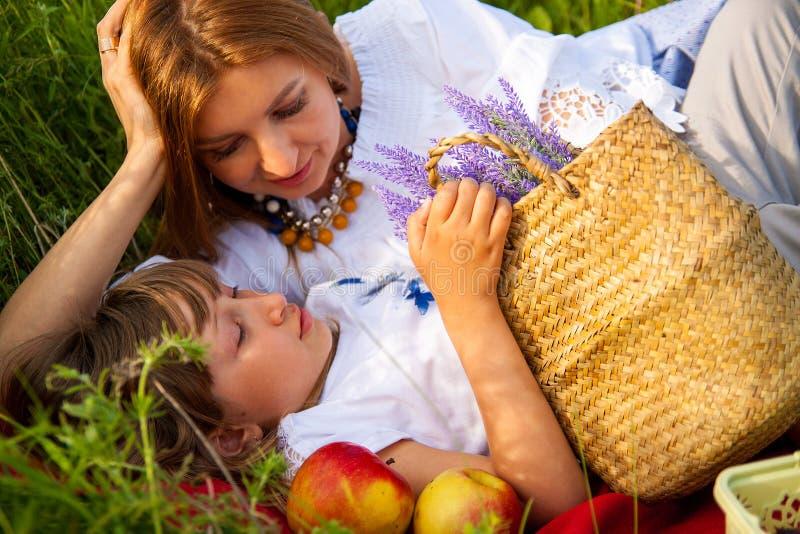 Härlig ung moder och hennes dotter i vit som har gyckel på blommafältet arkivfoto