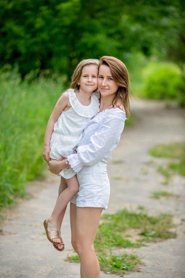 Härlig ung moder och hennes lilla dotter i den vita klänningen som har gyckel i en picknick De står på en väg i parkerar, mamman  royaltyfri foto