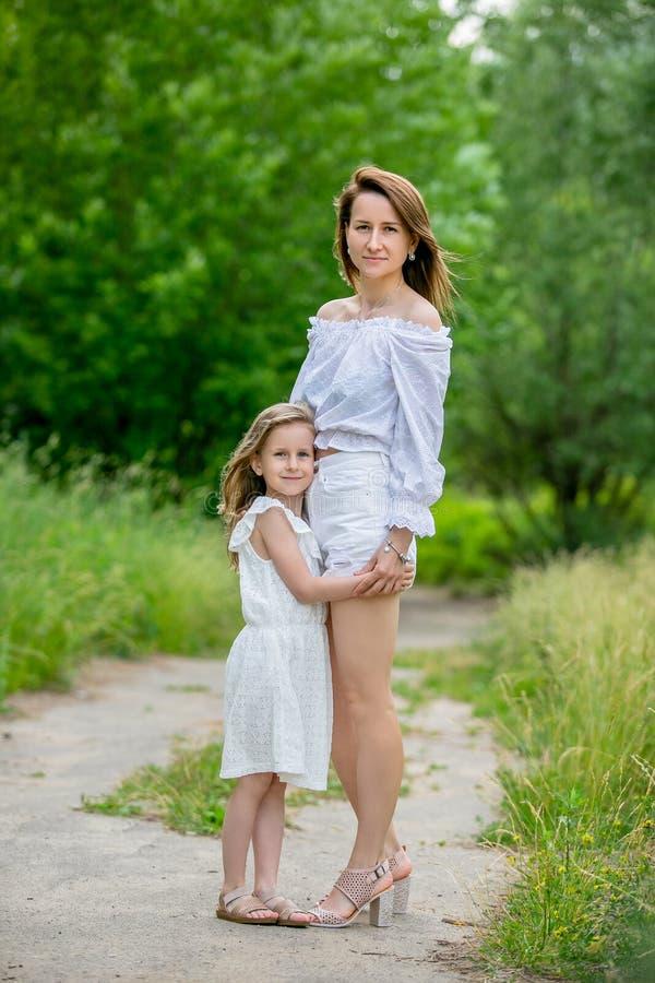 Härlig ung moder och hennes lilla dotter i den vita klänningen som har gyckel i en picknick De står på vägen i parkerar och arkivbild