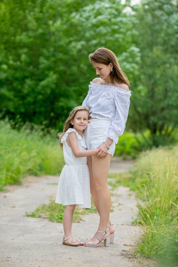 Härlig ung moder och hennes lilla dotter i den vita klänningen som har gyckel i en picknick De står på vägen i parkerar och royaltyfri foto