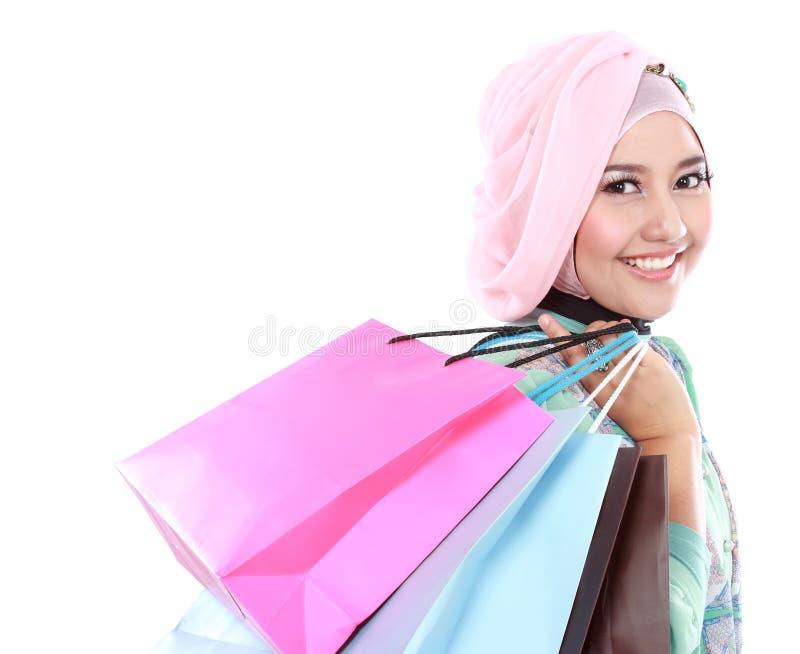 Härlig ung muslimkvinna som rymmer några shoppingpåsar arkivbilder