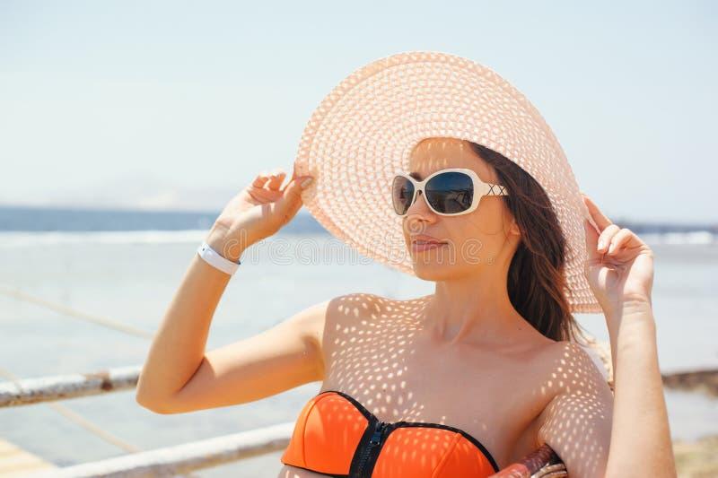Härlig ung nätt kvinna i solglasögon och den vita hatten vid havet fotografering för bildbyråer