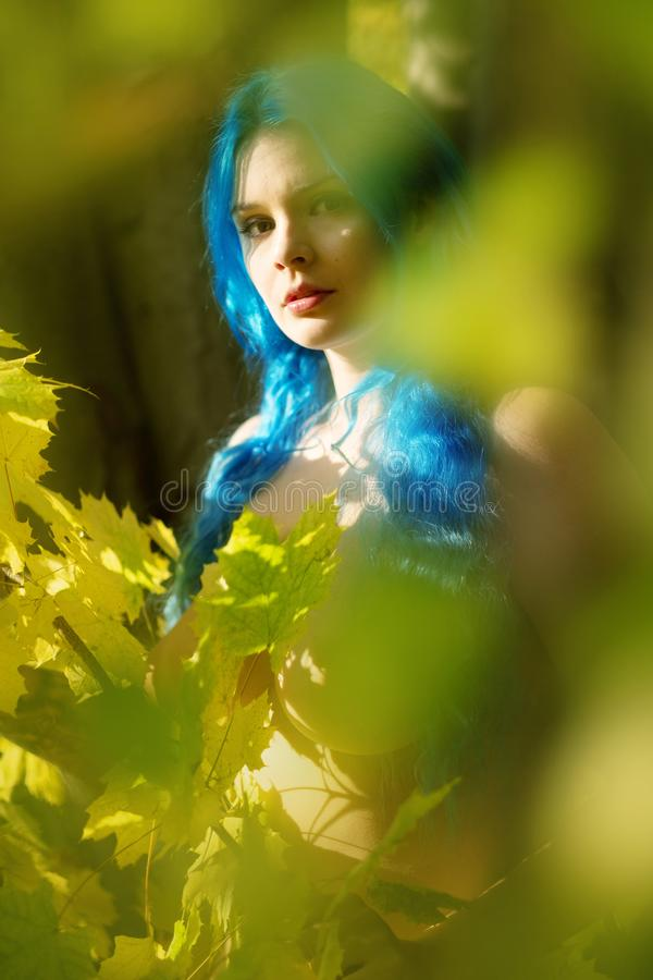 Härlig ung okonventionell kvinna Emo med individuella blåa hår, jämliken ut i höstskog mellan gröna gula sidor royaltyfri foto