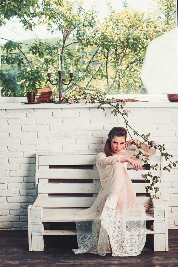 Härlig ung parisisk kvinna i den långa vita siden- klänningen som sitter på bänksommardagen fotografering för bildbyråer