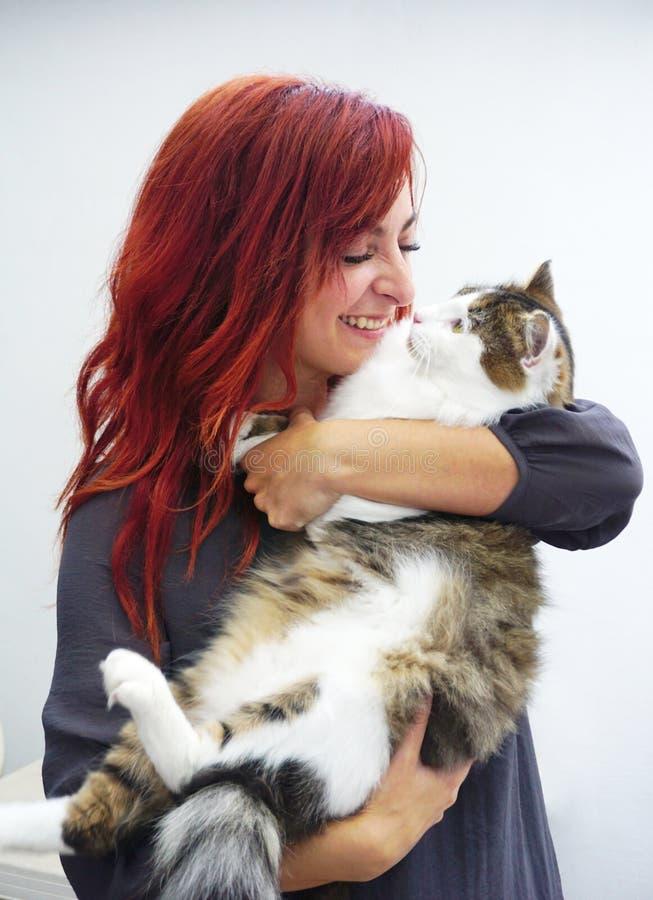 Härlig ung röd haired kvinna som kelar den gulliga stamträdhusdjurkatten royaltyfri fotografi