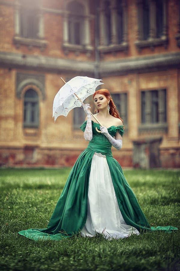 Härlig ung rödhårig flicka i en medeltida grön klänning royaltyfria foton