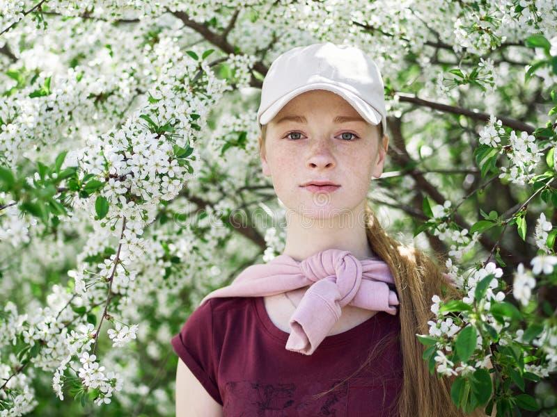 Härlig ung rödhårig mankvinna, i att blomstra trädgården tät stående upp arkivfoton