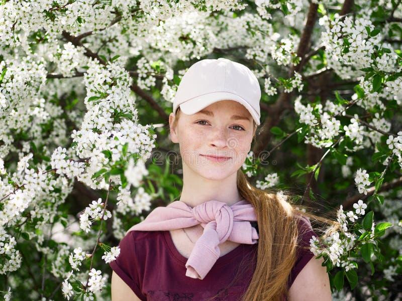 Härlig ung rödhårig mankvinna, i att blomstra trädgården tät stående upp arkivbild