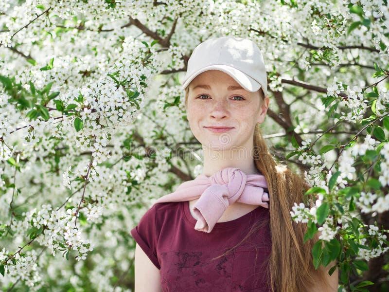 Härlig ung rödhårig mankvinna, i att blomstra trädgården tät stående upp royaltyfri foto