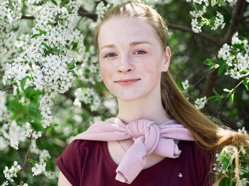 Härlig ung rödhårig mankvinna, i att blomstra trädgården tät stående upp fotografering för bildbyråer