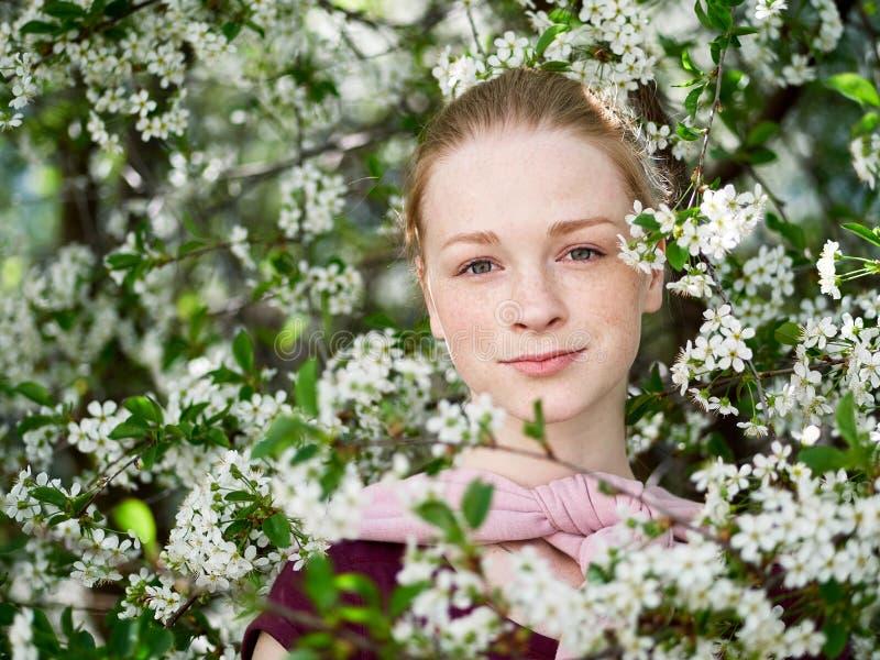Härlig ung rödhårig mankvinna, i att blomstra trädgården tät stående upp royaltyfri fotografi